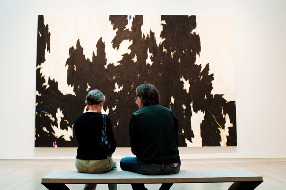 Art enthusiasts sit in front of an original Clyfford Still.
