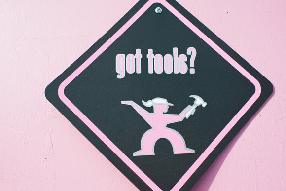 A sign hangs on the pink door to Tomboy Tools.