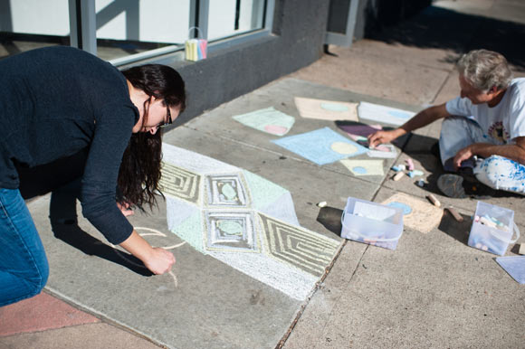 Outside of Spark Gallery in the Santa Fe Arts District, artists draw chalk art on the sidewalk.