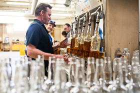 Stranahan's head distiller, Rob Dietrich, fills bottles with whiskey. He can fil up to 19 bottles per minute.