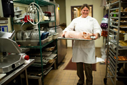 Panzano's executive chef Elise Wiggins carries out a butchered and cured pig that will be baked and served as suckling porchetta.