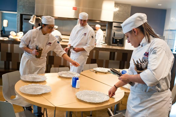 Students set the tables during the Food Production and Service 2 class.