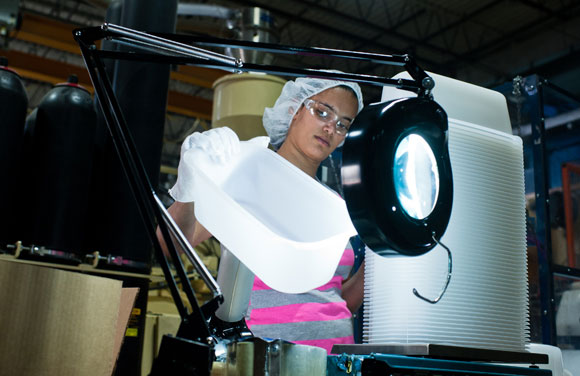 An employee quality checks products at Intertech Plastics.