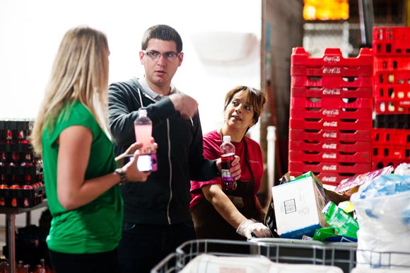 Eric Berlinberg and Tonya Tooley talk with a Coca-Cola employee about the recycling center.