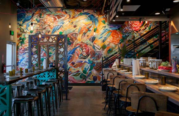 Los Chingones greets patrons with a colorfully chaotic floor-to-ceiling splatter painting.
