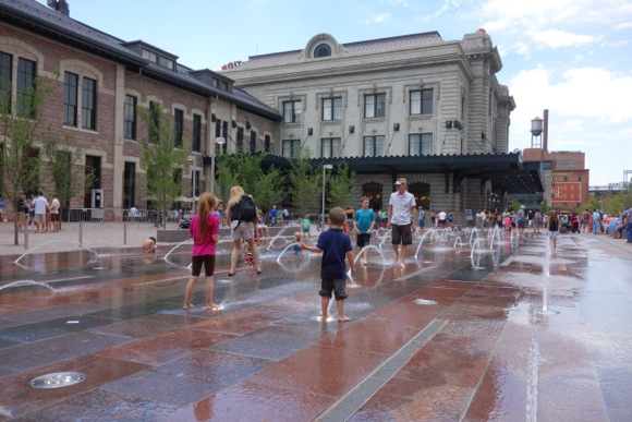 Kids frolic in the new fountains on opening day.