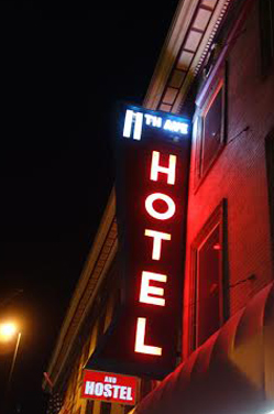 The neon sign for the 11th Avenue Hotel and Hostel lights up Broadway.