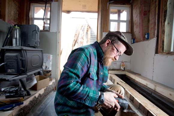 Marcus Hyde finishes a storage bench in a tiny house.