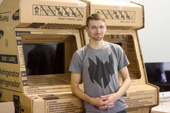 Justin Gitlin stands with cardboard arcade games from OhHeckYeah installations.