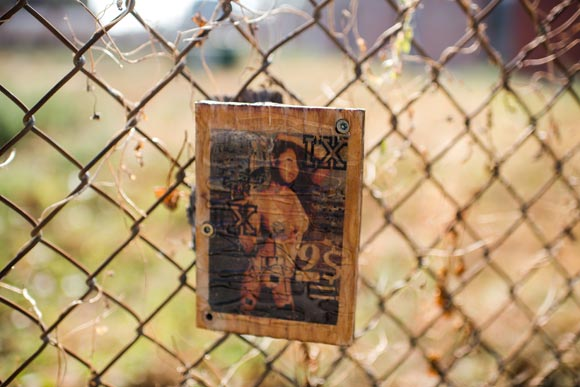 A random piece of art hangs from a fence.