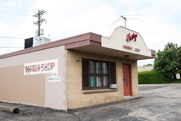 Charley's Barbershop, a small, standalone brick building with cursive red writing and a matching red door, facing the eastward traffic of I-70.