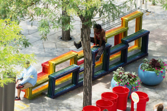 A performer uses Nick Fish's Rainbow Street Seating as a stage.