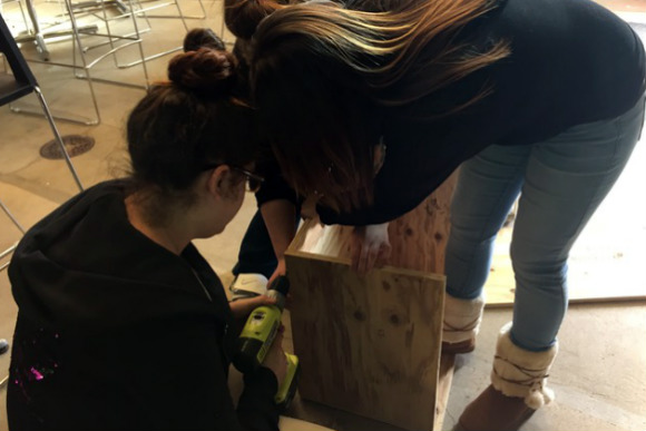 RiseUp students build a Little Free Library.