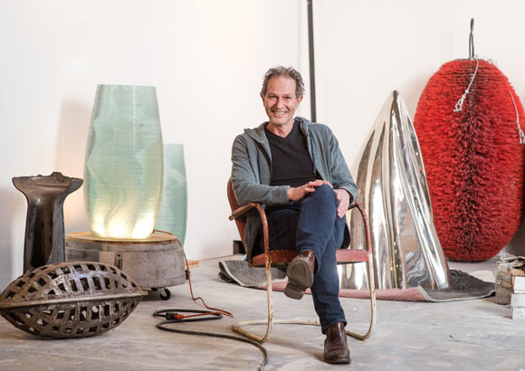 Lawrence Argent, 60, sits amid various parts of scultpures and artwork.