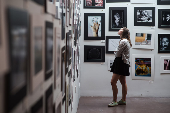 A young woman looks at the photographs on display in MCA Denver's Teen Lounge.