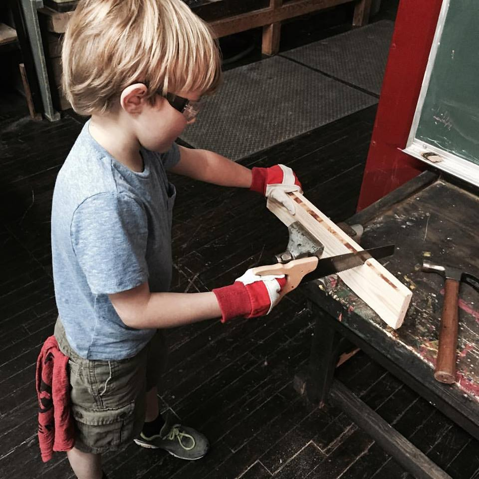A child saws away at Craftsman & Apprentice.