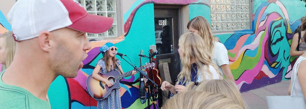 Young musician Emelise performs on the street during First Friday Art Walk in Denver's Art District on Santa Fe