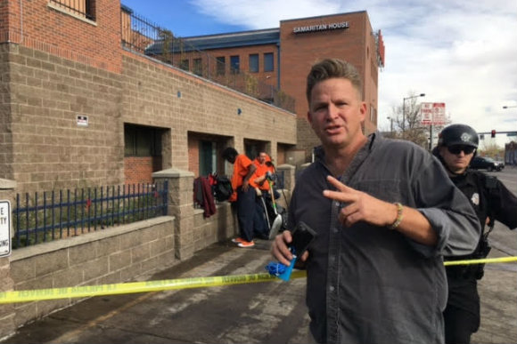 PJ D'Amico stands vigil at a homeless sweep in Denver.
